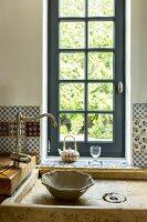 Traditioneller Spültisch mit nostalgischer Armatur vor Sprossenfenster