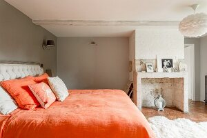 Double bed with orange bed linen in traditional bedroom with masonry, disused fireplace