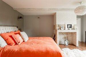 Doppelbett mit orangefarbener Bettwäsche in traditionellem Schlafzimmer mit gemauertem, stillgelegtem Kamin