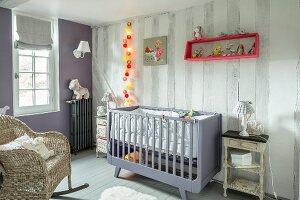 Gitterbett, Korbschaukelstuhl und beleuchtete Lichterkette in Kinderzimmer mit nostalgischem Flair