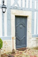 Elegant blue-grey front door of traditional half-timbered house