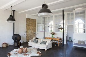 Animal-skin rug, tree stump tables and wood-burning stove in lounge area