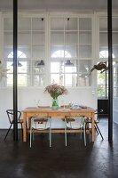 Dining table, black steel pillars and interior windows in loft apartment