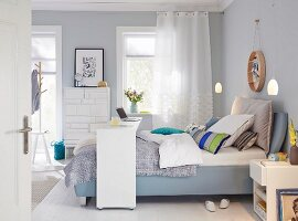 A boxspring bed with a bridge bed in a bedroom in shades of blue