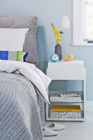 A white bedside table next to a box spring bed