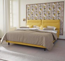 A yellow boxspring bed with a sand-coloured cover against framed Japanese-style wallpaper