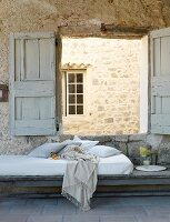 Cushion and blanket on mattress below open window shutters with view of stone wall