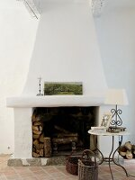 White chimney breast, delicate side table and terracotta floor tiles