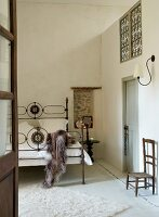 Antique iron bed, bedside table and wooden chair below sconce lamp in high-ceilinged bedroom