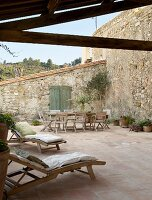 Wooden loungers, table and chairs on Mediterranean terrace with terracotta floor tiles and stone walls