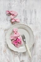 Hand-made pink bows on white plate
