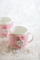 White mugs with hand-made pink mug cosies decorated with heart-shaped buttons