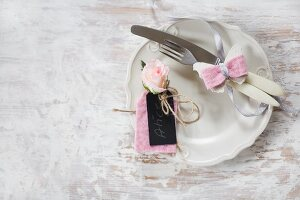 Hand-made place card made from black cardboard, pink felt and pink flower next to cutlery decorated with felt butterfly