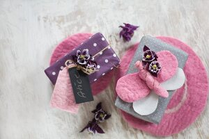 Wrapped gifts decorated with flowers, hand-made tags and felt butterflies on pin mats