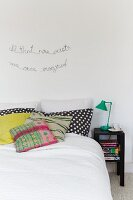 Various scatter cushions on bed below motto on wall