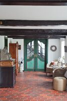 Green double doors, wicker armchairs, antique furniture and terracotta floor tiles in hallway of renovated farmhouse