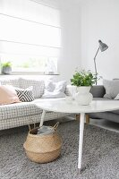 White coffee table and sofa with checked upholstery below window with closed roller blind