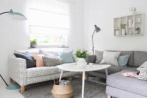 Wohnzimmerecke mit weissem Couchtisch und Sofas mit verschiedenen Bezügen vor Fenster mit geschlossenem Rollo