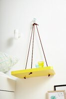 DIY shelf painted yellow hung on wall from ropes and used as bedside table