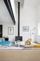 Black steel girder and wood-burning stove with tall stove pipe in eclectic living area