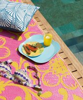 Papaya and drink on tray and cushions on patterned blanket on wooden deck adjoining pool