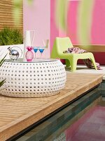 Refreshing drinks on modern outdoor side table on wooden deck next to pool