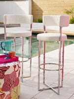 Modern bar stools with white leather covers and chrome frames on terrace next to pool