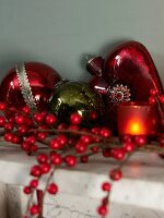 Branches of red berries, tealight holder and Christmas baubles on mantelpiece