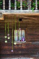 Alliums hung in front of lattice window in façade of rustic farmhouse