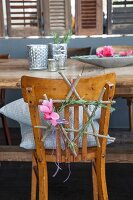 Star made from twigs decorated with rosemary and cyclamen on chair backrest