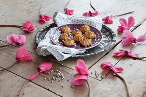 Romantic arrangement of cyclamen flowers around plate of macaroons