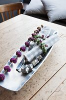Branch of purple beautyberry and linen napkin with rosemary napkin ring in long dish