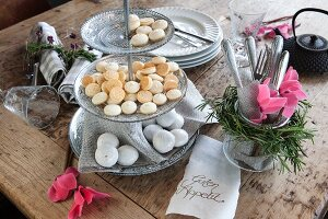 Romantic arrangement of pink cyclamen and biscuits on cake stand on wooden table