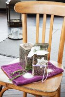 Rosemary bath salts in decorative tins on purple towel arranged on wooden chair