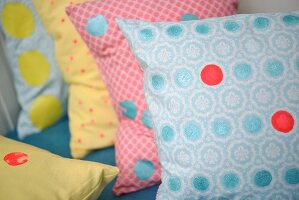 Cushion covers decorated with colourful spots of paint