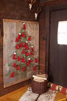Tree-shaped, hand-made Advent calendar made from green cord on rustic wooden panel