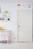 Decorative wall plates above white panelled door, painted chest of drawers and String shelves in living area