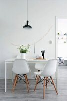Classic chairs around white dining table below black pendant lamp