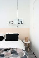 Black pillows on white bed linen below shelf on wall with pink painted dado