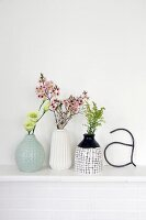 Retro arrangement of vases and flowers on white mantelpiece