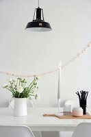 Vase of ranunculus and beaker of black drinking straws on white dining table in front of pink garland on wall