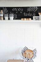 Bread basket in front of white wall tiles below kitchen shelf with chalkboard back wall