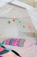 Colourful crocheted garland and pastel bed linen on pretty bed with white canopy in girl's bedroom