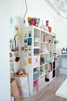 Storage boxes, books and accessories on white open-fronted shelves in attic room