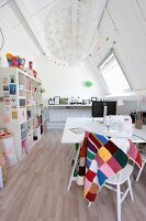 Open-fronted white shelving, desk and sewing machine in attic work room
