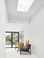 Blue and yellow, 50s retro armchairs with wooden frames against white brick wall in modern interior