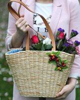 Frau hält Korbtasche mit blühenden Schnittblumen