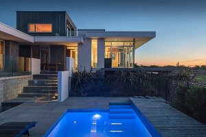 Pool outside contemporary house with illuminated interior at twilight