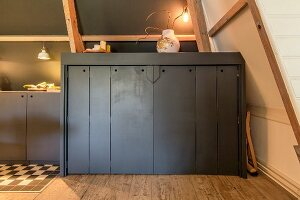 Half-height fitted cupboards painted dark grey under sloping ceiling with exposed wooden roof beams