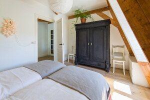 Zwei Betten mit grauer Tagesdecke und schwarz gebeizter Bauernschrank im Dachzimmer